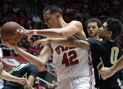 Utah's Jason Washburn is fouled by Colorado's Askia Booker. (AP)