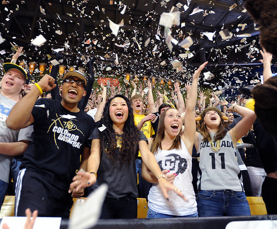 Shreyash Pradhan, left, Jariya Phanpaktra, Kristen Conrad, and Ashton Horowitz, throw up paper with the student section after the Buffs score their first basket.<br /> University of Colorado basketball fans raise the roof at the CU Air Force on November 25th, 2012.<br /> Cliff Grassmick / November 25, 2012
