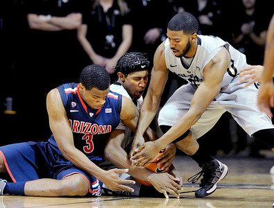 Kevin Parrom, left, of Arizona, tries to get the ball from Xavier Johnson and enemy Adams of CU. For more photos of the game, go to www.dailycamera.com. Cliff Grassmick / February 14, 2013