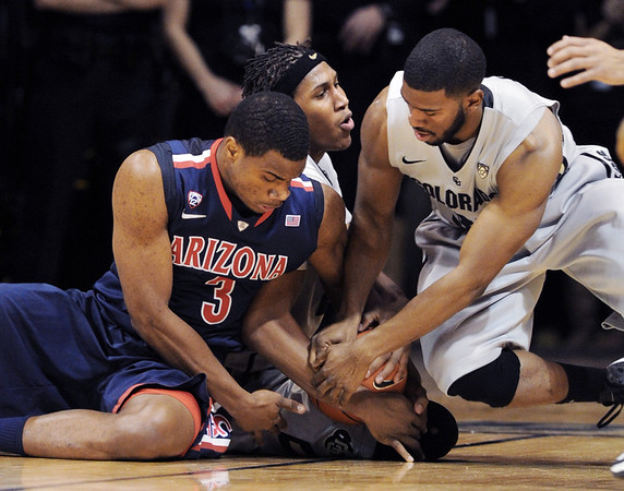 "Kevin Parrom, left, of Arizona, tries to get the ball from Xavier Johnson and enemy Adams of CU.<br /> For more photos of the game, go to  <a href=""http://www.dailycamera.com"">http://www.dailycamera.com</a>.<br /> Cliff Grassmick / February 14, 2013"