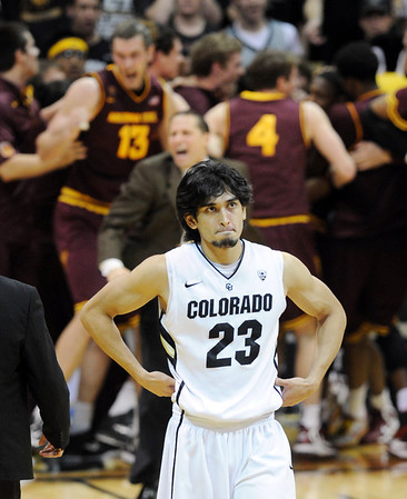 """A disappointed Sabatino Chen of Colorado walks off  the court after the overtime loss, while Arizona State players celebrate in the background during the  February 16th, 2013 game in Boulder.<br /> For more photos of the game, go to  <a href=""""http://www.dailycamera.com"""">http://www.dailycamera.com</a>.<br /> Cliff Grassmick / February 16, 2013"""