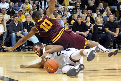 Evan Gordan (10) of Arizona State falls on Jeremy Adams of Colorado going for a loose ball during the first half of the February 16th, 2013 game in Boulder. For more photos of the game, go to www.dailycamera.com. Cliff Grassmick / February 16, 2013