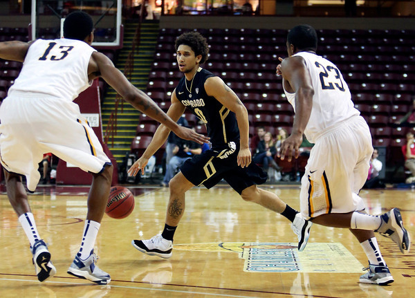 Colorado's Askia Booker, center, drives to the basket past Murray State's Brandon Garrett, left, and Dexter Fields, right, during an NCAA college basketball game at the Charleston Classic, Sunday, Nov. 18, 2012, in Charleston, S.C. Colorado won 81-74 and Booker was named tournament MVP. (AP Photo/Alice Keeney)
