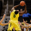 Oregon's Olu Ashaolu, center, gets a rebound as Colorado's Austin Dufault, left, and Nate Tomlinson look on during the first half of an NCAA college basketball game at the Pac-12 conference championship in Los Angeles, Thursday, March 8, 2012. (AP Photo/Jae C. Hong)