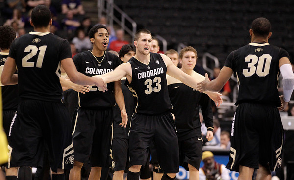 Colorado's Andre Roberson, left, and Colorado's Carlon Brown, right, are greeted by teammates during the second half of an NCAA college basketball game against the Oregon at the Pac-12 conference championship in Los Angeles, Thursday, March 8, 2012. Colorado won 63-62. (AP Photo/Jae C. Hong)