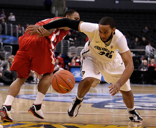 Colorado's Carlon Brown, right, goes after the loose ball as Utah's Chris Hines watches during the second half of an NCAA college basketball game at the Pac-12 conference championship in Los Angeles, Wednesday, March 7, 2012. Colorado won 53-41. (AP Photo/Jae C. Hong)
