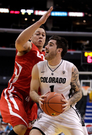 Utah's Javon Dawson, left, pressures Colorado's Nate Tomlinson during the first half of an NCAA college basketball game at the Pac-12 conference championship in Los Angeles, Wednesday, March 7, 2012. (AP Photo/Jae C. Hong)