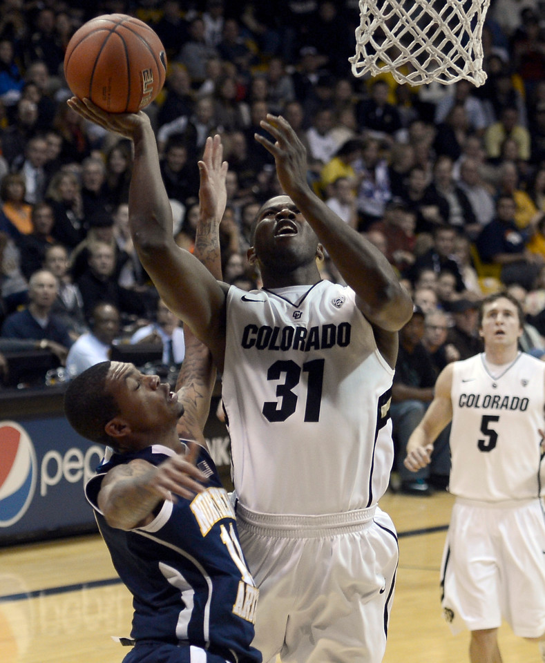 "University of Colorado's Jeremy Adams takes a shot over Gabe Rogers during a game against Northern Arizona on Friday, Dec. 21, at the Coors Event Center on the CU campus in Boulder. For more photos of the game go to  <a href=""http://www.dailycamera.com"">http://www.dailycamera.com</a><br /> Jeremy Papasso/ Camera"