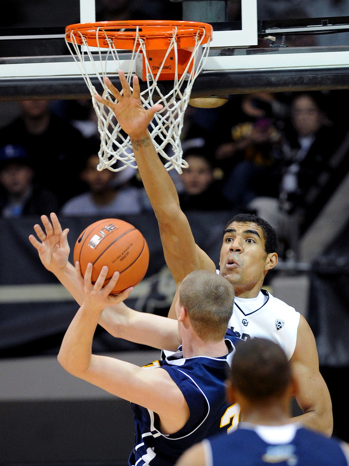 Josh Scott of Colorado, tries to block the shot of Max Jacobsen of Northern Arizona during the first half of the December 21, 2012 game in Boulder.<br /> Cliff Grassmick / December 21, 2012