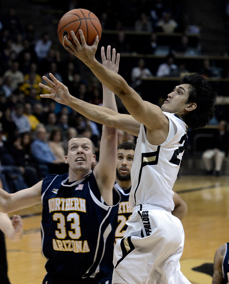 "University of Colorado's Sabatino Chen goes for a layup over Max Jacobsen during a game against Northern Arizona on Friday, Dec. 21, at the Coors Event Center on the CU campus in Boulder. For more photos of the game go to  <a href=""http://www.dailycamera.com"">http://www.dailycamera.com</a><br /> Jeremy Papasso/ Camera"