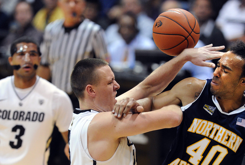 Shane Harris-Tunks, left, of Colorado and Ben Olayinka of Northern Arizona, battle under the basket during the second half of the December 21, 2012 game in Boulder.<br /> Cliff Grassmick / December 21, 2012
