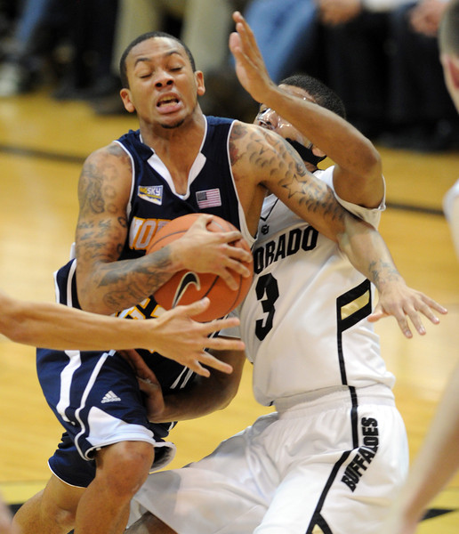 Gabe Rogers of Northern Arizona, drives past Xavier Talton of Colorado during the first half of the December 21, 2012 game in Boulder.<br /> Cliff Grassmick / December 21, 2012