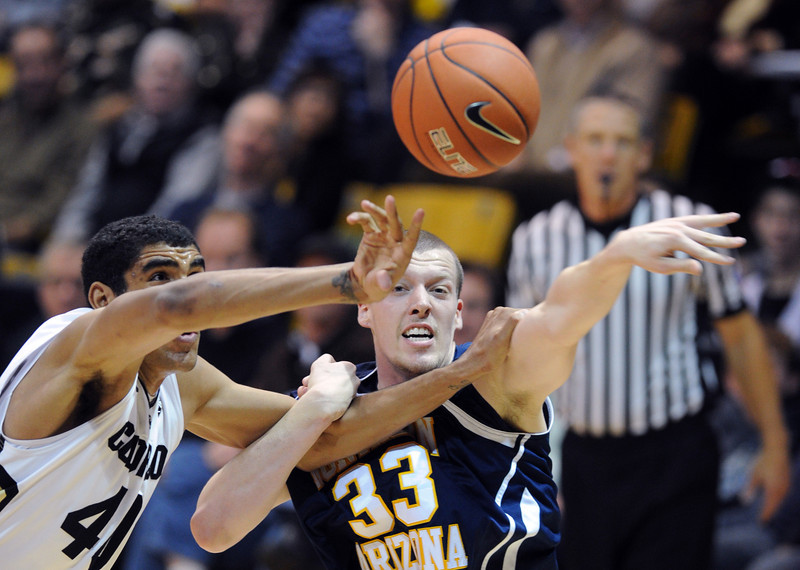 Josh Scott, left, of Colorado, knocks the ball from Max Jacobsen of Northern Arizona during the first of the December 21, 2012 game in Boulder.<br /> Cliff Grassmick / December 21, 2012
