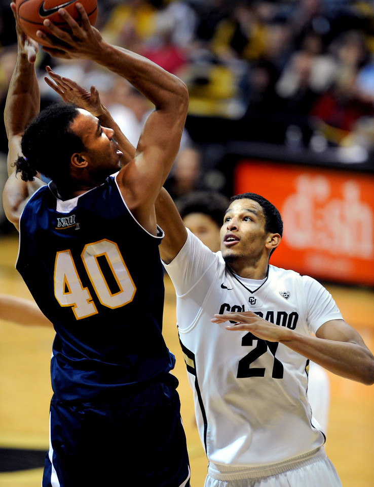 Ben Olayinka (40) of Northern Arizona, tries to shoot over Andre Roberson of Colorado during the first half of the December 21, 2012 game in Boulder.<br /> Cliff Grassmick / December 21, 2012