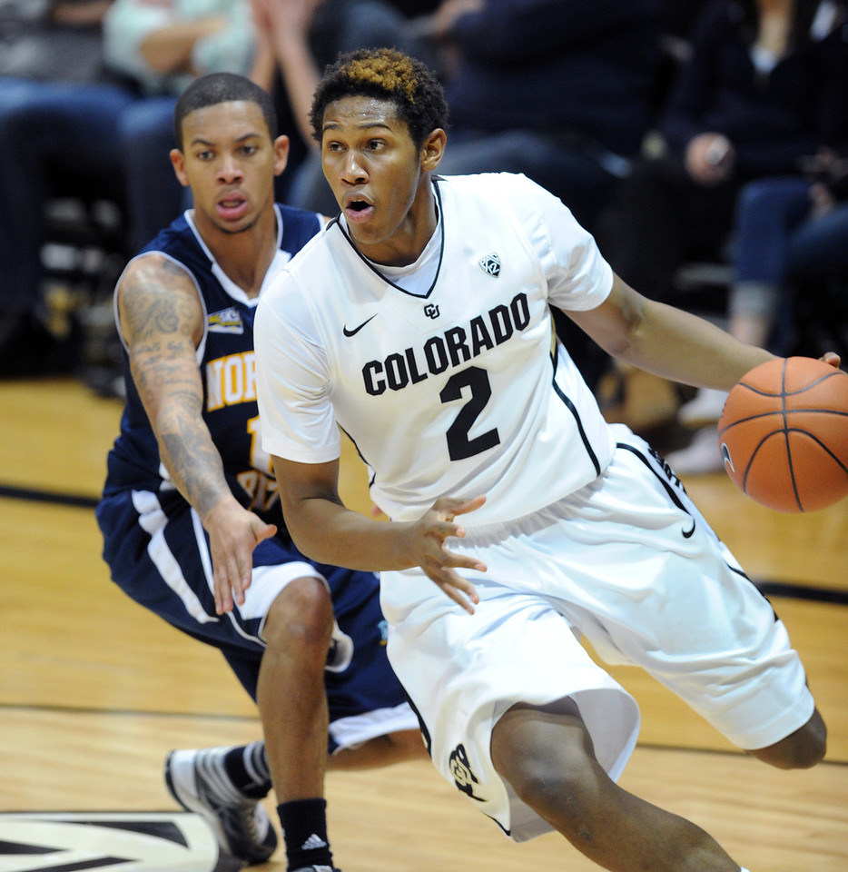 Xavier Johnson of CU drives past DeWayne Russell of NAU during the second half of the December 21, 2012 game in Boulder.<br /> Cliff Grassmick / December 21, 2012