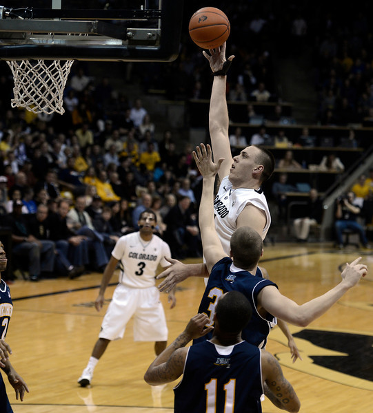 "University of Colorado's Shane Harris-Tunks takes a shot over Max Jacobsen during a game against Northern Arizona on Friday, Dec. 21, at the Coors Event Center on the CU campus in Boulder. For more photos of the game go to  <a href=""http://www.dailycamera.com"">http://www.dailycamera.com</a><br /> Jeremy Papasso/ Camera"