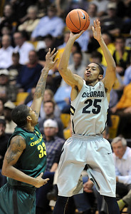 Spencer Dinwiddie of CU shoots on Carlos Emory of Oregon during the second half of the March 7, 2013 game in Boulder. For more photos of the game, go to www.dailycamera.com. Cliff Grassmick / March 7, 2013