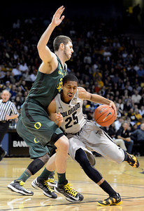 Spenser Dinwiddie of Colorado drives on Ben Carter of Oregon during the first half of the March 7, 2013 game in Boulder. For more photos of the game, go to www.dailycamera.com. Cliff Grassmick / March 7, 2013