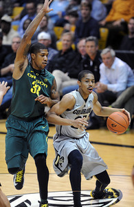 Spencer Dinwiddie of CU drives on Carlos Emory of Oregon during the second half of the March 7, 2013 game in Boulder. For more photos of the game, go to www.dailycamera.com. Cliff Grassmick / March 7, 2013
