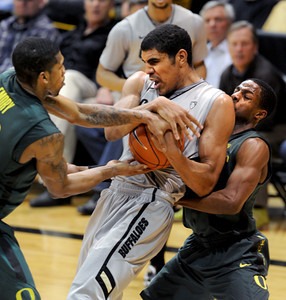 Carlos Emory, left, and Johnathan Loyd, both of Oregon, try to steal the ball from Josh Scott of CU during the second half of the March 7, 2013 game in Boulder. For more photos of the game, go to www.dailycamera.com. Cliff Grassmick / March 7, 2013