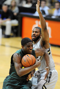 Damyean Dotson of Oregon drives past Jeremy Adams of Colorado during the first half of the March 7, 2013 game in Boulder. For more photos of the game, go to www.dailycamera.com. Cliff Grassmick / March 7, 2013