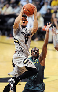 Askia Booker of Colorado prepares to pass off past Johnathan Loyd of Oregon during the second half of the March 7, 2013 game in Boulder. For more photos of the game, go to www.dailycamera.com. Cliff Grassmick / March 7, 2013