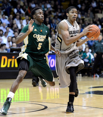 "University of Colorado's Spencer Dinwiddie drives past Jon Octeus during a game against Colorado State University on Wednesday, Dec. 5, at the Coors Event Center on the CU campus in Boulder. CU won 70-61. For more photos of the game go to  <a href=""http://www.dailycamera.com"">http://www.dailycamera.com</a><br /> Jeremy Papasso/ Camera"