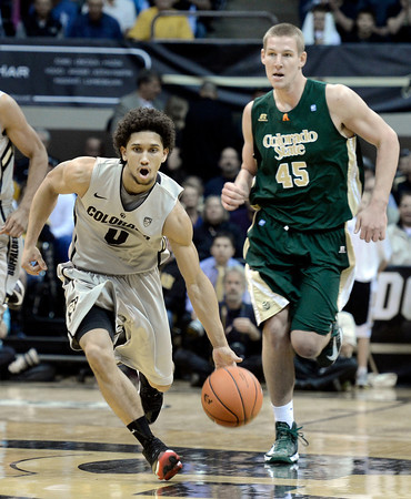 """University of Colorado's Askia Booker dribbles past Colton Iverson during a game against Colorado State University on Wednesday, Dec. 5, at the Coors Event Center on the CU campus in Boulder. CU won 70-61. For more photos of the game go to  <a href=""""http://www.dailycamera.com"""">http://www.dailycamera.com</a><br /> Jeremy Papasso/ Camera"""