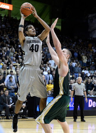 "University of Colorado's Josh Scott takes a shot over Colton Iverson during a game against Colorado State University on Wednesday, Dec. 5, at the Coors Event Center on the CU campus in Boulder. CU won 70-61. For more photos of the game go to  <a href=""http://www.dailycamera.com"">http://www.dailycamera.com</a><br /> Jeremy Papasso/ Camera"