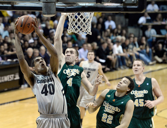 """University of Colorado's Josh Scott takes a shot over Pierce Hornung, No. 4, and Dorian Green, No. 22, during a game against Colorado State University on Wednesday, Dec. 5, at the Coors Event Center on the CU campus in Boulder. For more photos of the game go to  <a href=""""http://www.dailycamera.com"""">http://www.dailycamera.com</a><br /> Jeremy Papasso/ Camera"""