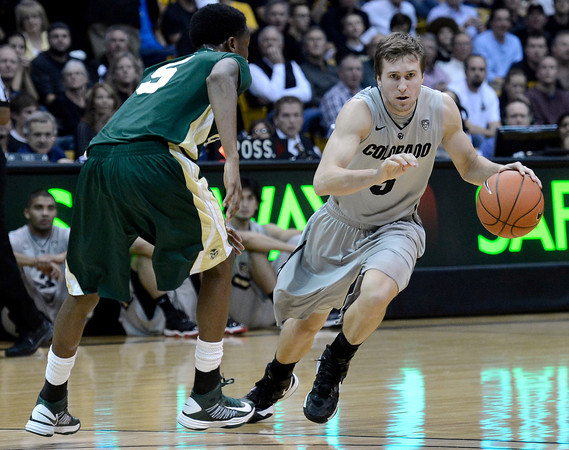 """University of Colorado's Eli Stalzer drives past Jon Octeus during a game against Colorado State University on Wednesday, Dec. 5, at the Coors Event Center on the CU campus in Boulder. CU won 70-61. For more photos of the game go to  <a href=""""http://www.dailycamera.com"""">http://www.dailycamera.com</a><br /> Jeremy Papasso/ Camera"""