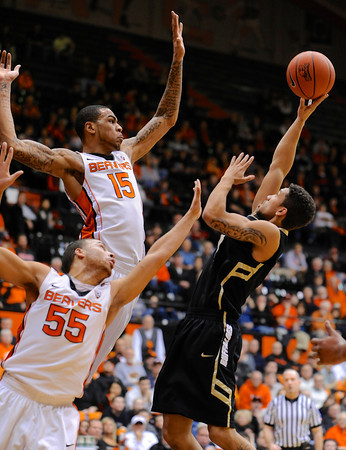 Colorado's Askia Booker, right, shoots against Oregon State's Eric Moreland (15) and Roberto Nelson (55) during the first half of an NCAA college basketball game in Corvallis, Ore., Sunday, Feb. 10, 2013. (AP Photo/Greg Wahl-Stephens)