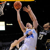 UCLA forward Travis Wear, center, puts up a shot as Colorado forward Austin Dufault, left, and forward Andre Roberson defend during the second half of their NCAA college basketball game on Saturday, Jan. 28, 2012, in Los Angeles. UCLA won 77-60. (AP Photo/Mark J. Terrill)