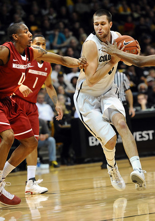 University of Colorado's #33 Austin Dufault dribbles against  Washington State's #0 Marcus Capers during their game at the Coors Events Center on the University of Colorado Boulder, Colo. Campus on Saturday January 7, 2012<br /> Photo by Paul Aiken  Jan 7, 2012