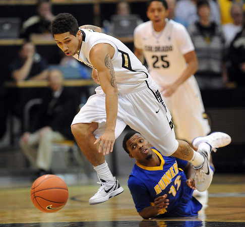 """Askia Booker of Colorado, takes off with a steal as Issiah Grayson of California State- Bakersfield looks on during the first half of the December 19, 2011 game in Boulder.<br /> <br /> For more photos of the game, go to  <a href=""""http://www.dailycamera.com"""">http://www.dailycamera.com</a>.<br /> December 19, 2011 / Cliff Grassmick"""