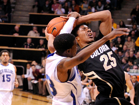 "University of Colorado's Spencer Dinwiddie gets fouled by Brandon Canady while going for a lay-up during a game against the University of New Orleans on Wednesday, Dec. 28, at the Coors Event Center on the CU campus in Boulder. For more photos of the game go to  <a href=""http://www.dailycamera.com"">http://www.dailycamera.com</a><br />  Jeremy Papasso/ Camera"