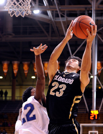 """University of Colorado's Sabatino Chen goes for a shot over Colby Barnes, No. 22, during a game against the University of New Orleans on Wednesday, Dec. 28, at the Coors Event Center on the CU campus in Boulder. For more photos of the game go to  <a href=""""http://www.dailycamera.com"""">http://www.dailycamera.com</a><br />  Jeremy Papasso/ Camera"""