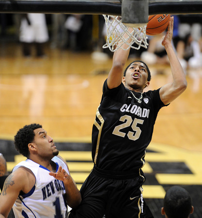 """Spencer Dinwiddie of Colorado goes up to score on Lenny Harmon of New Orleans during the first half of the December 28th, 2011 game in Boulder.<br /> For more photos of the game, go to  <a href=""""http://www.dailycamera.com"""">http://www.dailycamera.com</a>.<br /> December 28, 2011 / Cliff Grassmick"""