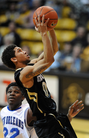 """Askia Booker of CU scores past Colby Barnes of New Orleans.<br /> For more photos of the game, go to  <a href=""""http://www.dailycamera.com"""">http://www.dailycamera.com</a>.<br /> December 28, 2011 / Cliff Grassmick"""