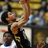 "Askia Booker of CU scores past Colby Barnes of New Orleans.<br /> For more photos of the game, go to  <a href=""http://www.dailycamera.com"">http://www.dailycamera.com</a>.<br /> December 28, 2011 / Cliff Grassmick"