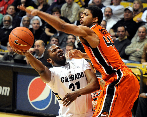 "University of Colorado's Jeremy Adams goes for a shot before being fouled by Oregon State's Devon Collier on Thursday, Feb. 2, during a game against Oregon State at the Coors Events Center in Boulder, Colo. For more photos of the game go to  <a href=""http://www.dailycamera.com"">http://www.dailycamera.com</a><br /> Jeremy Papasso/ Camera"
