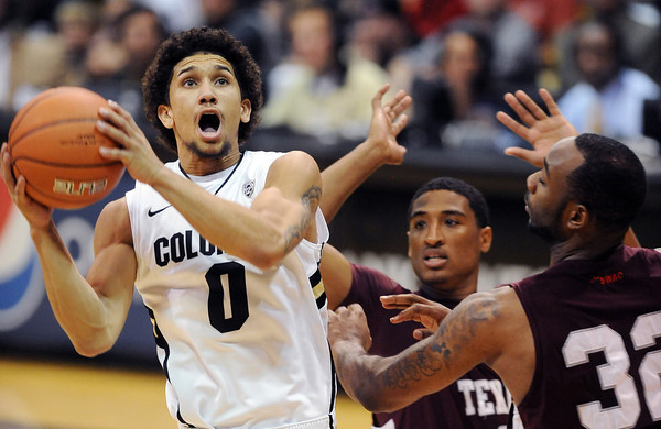 Askia Booker of CU drives to the basket on Madarious Gibbs and Aaron Clayborn, both of Texas Southern.<br /> Cliff Grassmick / November 27, 2012