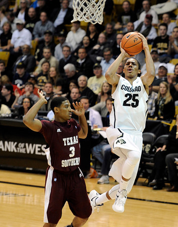 "University of Colorado's Spencer Dinwiddie takes a shot over Madarious Gibbs during a game against Texas Southern on Tuesday, Nov. 27, at the Coors Event Center on the CU campus in Boulder. For more photos of the game go to  <a href=""http://www.dailycamera.com"">http://www.dailycamera.com</a><br /> Jeremy Papasso/ Camera"