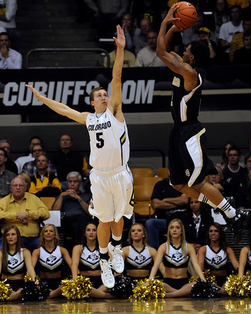 "University of Colorado's Eli Stalzer tries to block the shot of Karl Cochran during a game against the Wofford Terriers on Friday, Nov. 9, at the Coors Event Center on the CU campus in Boulder. For more photos of the game go to  <a href=""http://www.dailycamera.com"">http://www.dailycamera.com</a><br /> Jeremy Papasso/ Camera"