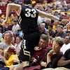 Colorado forward Austin Default leaps to avoid colliding with Arizona State fans, from left, Bill Schemers, his son William Schemers, 6, Bruce Sedlak and his wife Sue while chasing down a loose ball in the second half of an NCAA college basketball game Saturday, Feb. 11, 2012, in Tempe, Ariz. Colorado won 63-49.(AP Photo/Paul Connors)
