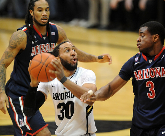 Carlon Brown of Colorado drives to the basket against Kevin Parrom (3), of Arizona during the first half of the January 21, 2012 game in Boulder.<br /> January 21, 2012 / Cliff Grassmick