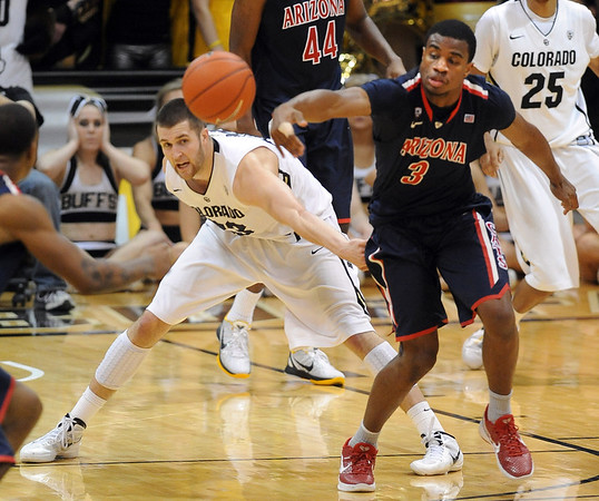 "Austin Dufault, left,  of Colorado, and Kevin Perry of Arizona, try to get to a loose ball during the second half of the January 21, 2012 game in Boulder.<br /> For more photos of the game, go to  <a href=""http://www.dailycamera.com"">http://www.dailycamera.com</a>.<br /> January 21, 2012 / Cliff Grassmick"