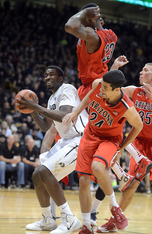 . Wesley Gordon of CU head fakes Rondae Hollis-Jefferson (23) of Arizona during the first half of the February 22, 2014 game in Boulder, Colo.  Cliff Grassmick / February 22, 2014