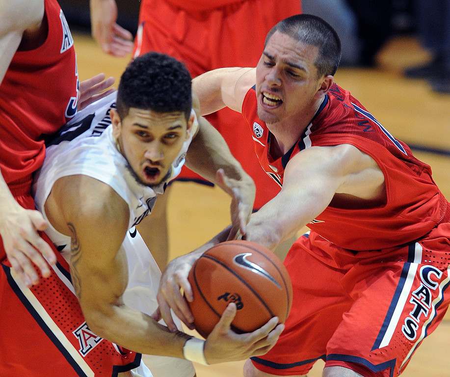. Askia Booker of CU tries to shoot with TJ McConnell  of Arizona defending during the second half of the February 22, 2014 game in Boulder, Colo.  Cliff Grassmick / February 22, 2014