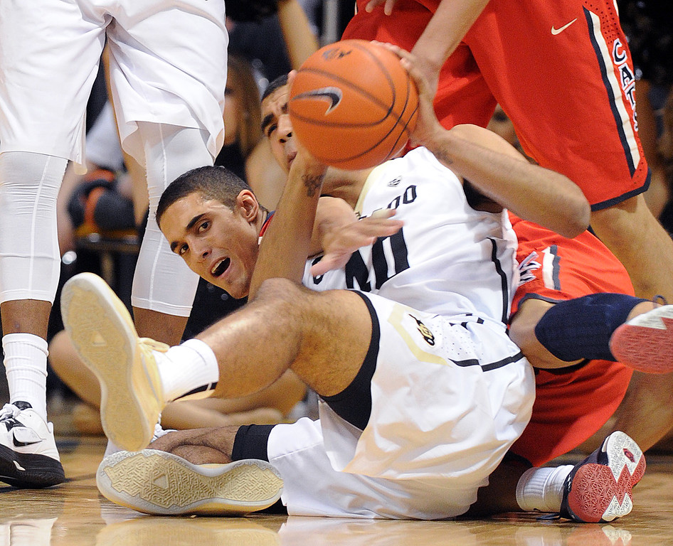 . Nick Johnson, left,  of Arizona and Josh Scott of Colorado,  go to the floor to get a loose ball during the first half of the February 22, 2014 game in Boulder, Colo.  Cliff Grassmick / February 22, 2014
